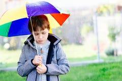 Sieben Jahre alte Junge, die am Regen stehen Stockbilder
