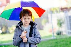Sieben Jahre alte Junge, die am Regen stehen Stockfoto
