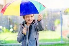 Sieben Jahre alte Junge, die am Regen stehen Lizenzfreie Stockfotografie