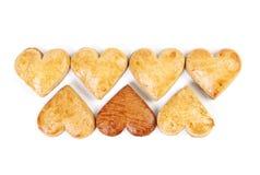 Sieben Lebkuchenherzen in zwei Reihen auf weißem Hintergrund Lizenzfreies Stockfoto