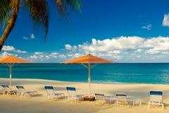 Sieben Meilen-Strand-Sonnenschirme und Sun-Ruhesessel stockfotos