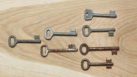 Sieben symmetrisch vereinbarte Schlüssel auf einem hölzernen Hintergrund stockfotografie