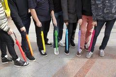 Sieben Teenager mit geschlossenen Regenschirmen in der Überführung Lizenzfreies Stockbild