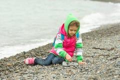 Siebenjähriges Mädchen, das auf einem Pebble Beach in der warmen Kleidung und mit Begeisterungsspielen mit Steinen sitzt Lizenzfreies Stockfoto