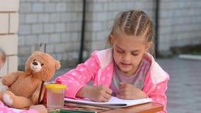 Siebenjähriges Mädchen mit Begeisterung zeichnet einen Bleistift auf dem Album und tut Zeichnung mit seiner Schwester in der Stra stock footage