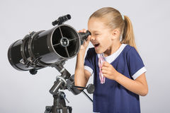Siebenjähriges Mädchen mit Interesse und dem offenen Untersuchung des Munds das Reflektorteleskop und den Blicken auf den Himmel Lizenzfreies Stockfoto