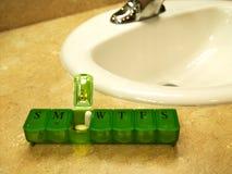 Siebentägiger grüner Pillenkasten mit Pillen sitzt auf Countertop lizenzfreie stockfotos