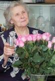 Siebzig Einjahresfrau mit bocal in der Hand Lizenzfreie Stockfotos