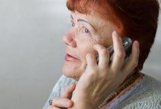 Siebzig Einjahresfrau mit Mobiltelefon Lizenzfreie Stockfotos