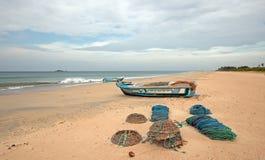 Sieci, oklepowie, kosze i arkany obok łodzi rybackiej na Nilaveli, wyrzucać na brzeg w Trincomalee Sri Lanka obrazy stock
