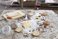 Sieda prego e mangi Sedia vuota davanti a varietà di formaggio Immagini Stock