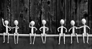 Siedem białych postaci siedzi na drewnianej półce w różnorodnych pozach zdjęcie stock