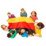 Siedem dzieciaków trzyma niemiec chorągwianego obsiadanie wokoło go Zdjęcie Stock