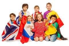 Siedem dzieciaków z flaga zawijać w różnych sztandarach Fotografia Stock