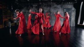 Siedem powabnych tancerzy kobiet tanczą w próbować salę, będący ubranym czerwone suknie, kłama na podłodze zbiory