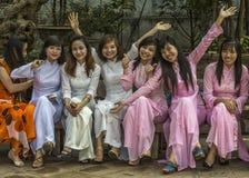 Siedem radosnych żeńskich uniwersyteckich seniorów ubierali w Ao Dai Zdjęcia Stock