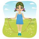 Siedem rok dziewczyny doskakiwania z omijać arkanę w lato parku Fotografia Stock