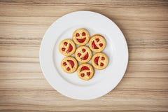Siedem round ciastek uśmiecha się twarze na białym talerzu, humorystycznym zdjęcie royalty free