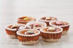 Siedem wyśmienicie domowej roboty mini cheesecakes z rozciekłą czekoladą i kolorowym cukierem kropią na drewnianym stole Zdjęcie Royalty Free