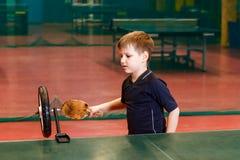 Siedmioletni dziecko w sport formie trenuje strajki w stołowym tenisie z pomocą symulanta na stole obraz stock