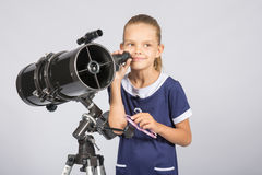 Siedmioletnia dziewczyny pozycja obok odbłyśnika teleskopu i spojrzenia w niebo tajemniczo Obraz Stock