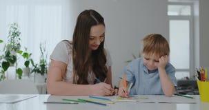 Siedzący przy stołem w żywym pokoju, młoda matka uczy jej syna trzymać ołówek i uczy remis zbiory