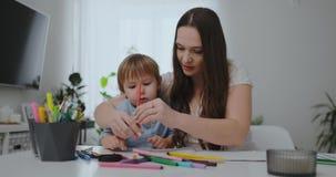 Siedzący przy stołem w żywym pokoju, młoda matka uczy jej syna trzymać ołówek i uczy remis zbiory wideo
