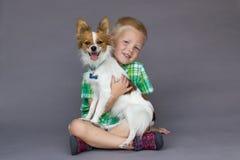 Siedząca chłopiec trzyma Papillon psa Zdjęcia Stock