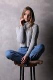Siedząca dziewczyna dotyka jej twarz w pulowerze Szary tło Zdjęcie Royalty Free