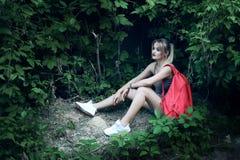 Siedząca dziewczyna jest ubranym szkła, drelichowi skróty, szara koszula z plecakiem Zdjęcia Stock