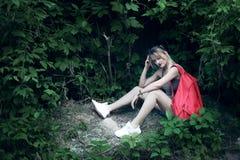 Siedząca dziewczyna jest ubranym szkła, drelichowi skróty, szara koszula z plecakiem Obrazy Stock