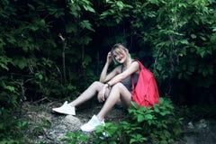 Siedząca dziewczyna jest ubranym szkła, drelichowi skróty, szara koszula z plecakiem Fotografia Royalty Free