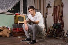 Siedząca młodego człowieka mienia butelka przy dżonka pokojem zdjęcie stock