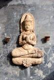 Siedząca ono modli się Buddha statua na kamiennej ścianie z małymi świeczka właścicielami zdjęcie royalty free