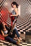 Siedzące i trwanie kobiety bawić się gitarę elektryczną w studiu Zdjęcie Stock