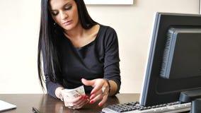 Siedzącego Młodego bizneswomanu Odliczająca gotówka na ręce zbiory wideo