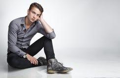 Siedzący atrakcyjny młody człowiek fotografia stock