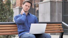Siedzący plenerowy, młody człowiek z szyja bólem pracuje na laptopie zbiory