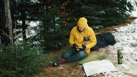 Siedzący puszek halny wzgórze obok zielonych drzew młody człowiek jest przyglądający dla nowej drogi Trzyma pastylkę, a zbiory wideo