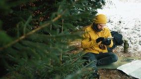 Siedzący puszek halny wzgórze obok zielonych drzew młody człowiek używa pastylkę zdjęcie wideo