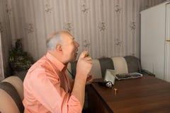 Siedzący starego człowieka opryskiwania Aftershave na jego twarzy Zdjęcie Stock