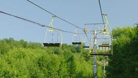Siedzenia narciarski dźwignięcie Ruszają się upwards przeciw tłu las zakrywający z lasowi wakacje w zbiory wideo
