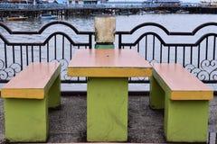 Siedzi ławkę w miejscu publicznym i przerzuca most nad rzeką zdjęcie stock