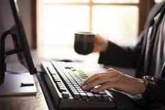 Siedzi i pracuje na komputerze, ?yczek kawa w ranku obrazy stock