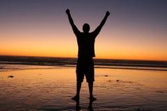 Sieg-Mann im Sonnenuntergang Stockfotografie