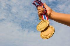 Siegerhand, die angehoben wird und zwei Goldmedaillen mit thailändischem Band gehalten ist Stockfotografie