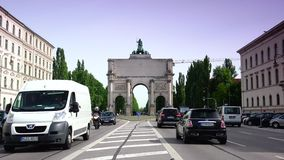 Siegestor gate in the background are landmarks of the Munich, Germany. Morning traffic on Ludwigstrasse boulevard in Munich, Germany. This broad avenue and the stock video footage