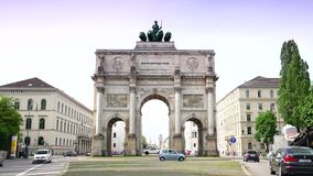 Siegestor gate in the background are landmarks of the Munich, Germany. Morning traffic on Ludwigstrasse boulevard in Munich, Germany. This broad avenue and the stock video