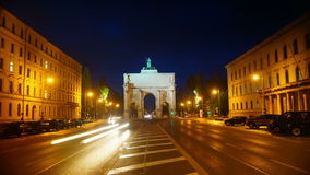 Siegestor gate in the background are landmarks of the Munich, Germany. Morning traffic on Ludwigstrasse boulevard in Munich, Germany. This broad avenue and the stock footage