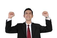 Siegreicher Geschäftsmann, der seine Hände, lokalisiert auf Weiß anhebt Stockbild